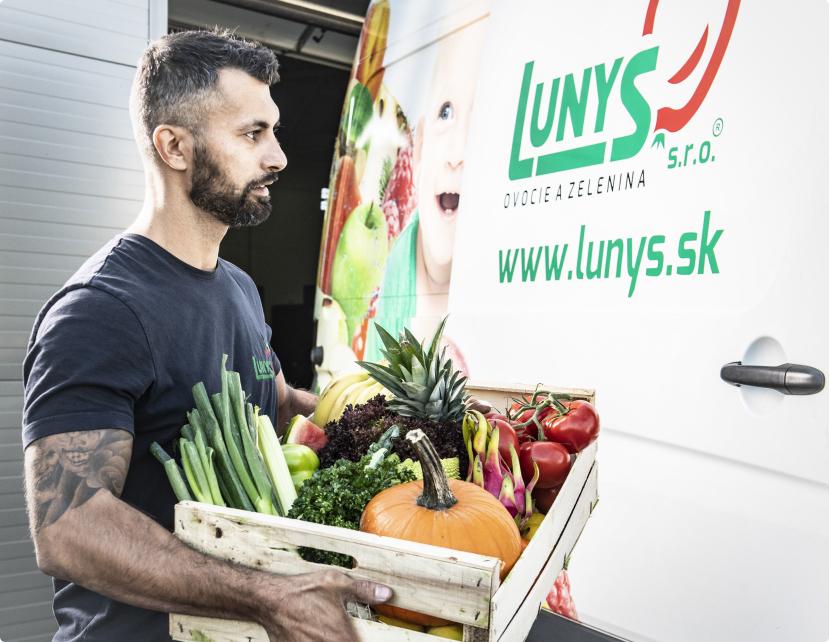 Svalovec z Lunysu nakladá bedničku plnú ovocia a zeleninu do auta na prepravu